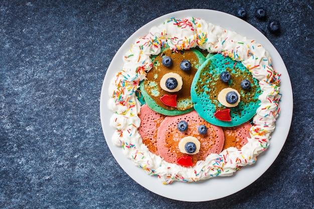 Mehrfarbige pfannkuchen mit früchten und schlagsahne für kinder auf einer weißen platte. pfannkuchen mit augen und mund für babynahrung.