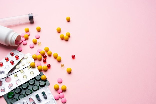 Mehrfarbige pillen in paketen medizinische versorgung gesundheitswesen rosa hintergrund
