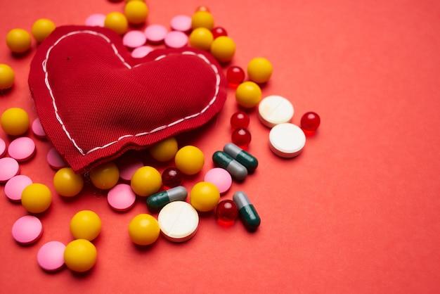 Mehrfarbige pillen weiches herz mit rotem hintergrund zur gesundheitsbehandlung