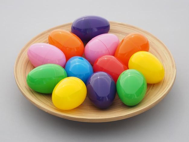 Mehrfarbige plastik-ostereier in einem teller auf grau.