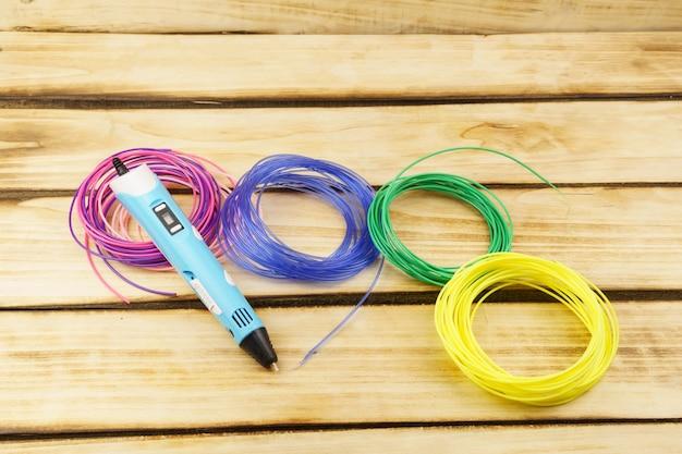 Mehrfarbige plastikfäden und 3d-stift auf einem hölzernen hintergrund.