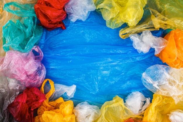 Mehrfarbige plastiktüten begrenzen rahmen auf blauem pet-filmhintergrund