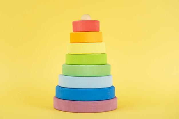 Mehrfarbige pyramide des babys in der mitte auf gelbem hintergrund
