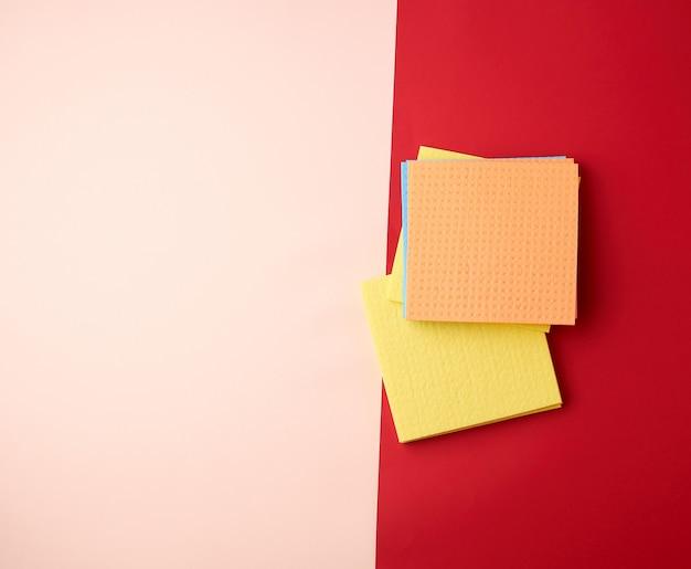 Mehrfarbige quadratische abwaschschwämme auf einem rot-beige