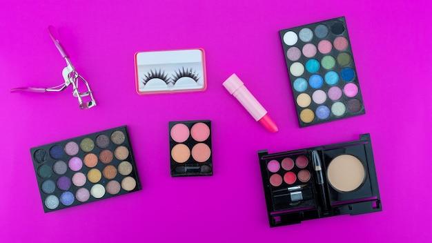 Mehrfarbige schöne lidschatten-palette und verschiedene kosmetische accessoires für make-up auf rosa hintergrund beauty-produkte make-up-kosmetik sommer-lidschatten