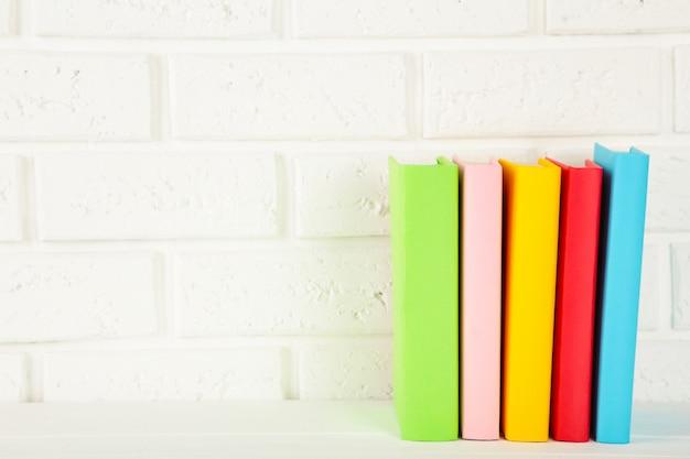Mehrfarbige schulbücher auf weißem hintergrund mit kopierraum.