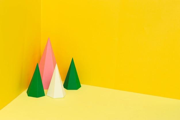 Mehrfarbige sechseckige papierpyramiden stehen in der ecke auf gelbem hintergrund papierkunst und handwerk
