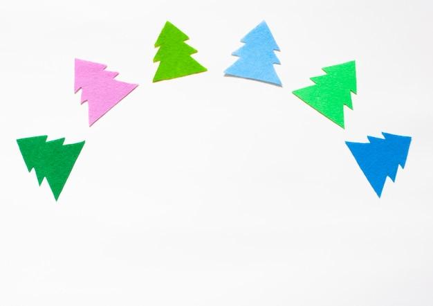 Mehrfarbige silhouetten von weihnachtsbäumen im halbkreis auf weiß