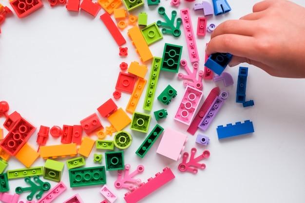 Mehrfarbige spielzeugblöcke zufällige farbige plastikbauklötze oder ziegelsteinspielzeug. konzept der bildung, entwicklung und wachstum. lernspielzeug für kreative kinder.