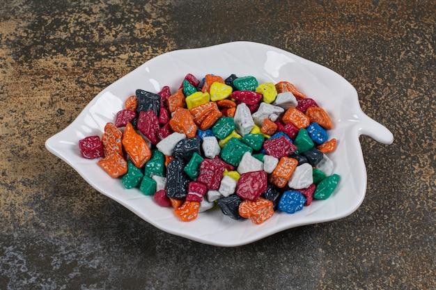 Mehrfarbige steinbonbons auf blattförmigem teller.