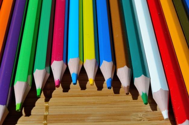 Mehrfarbige stifte, die durch einen bogen auf einem strohhalm ausgelegt sind.