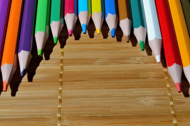 Mehrfarbige stifte, die von einem bogen auf einem strohhintergrund ausgelegt werden.