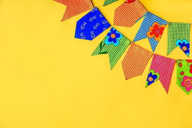 Mehrfarbige stofffahnen auf gelbem grund. dekorationen für den urlaub.