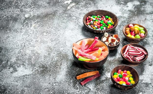 Mehrfarbige süßigkeiten, gelee und marshmallows in einer schüssel. auf einem rustikalen hintergrund.