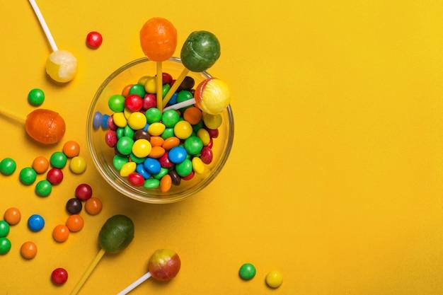 Mehrfarbige süßigkeiten und lutscher auf gelbem hintergrund