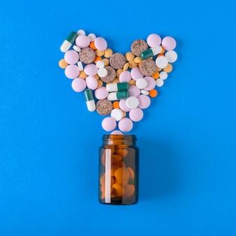 Mehrfarbige tabletten werden aus einem glasgefäß in form eines herzens auf blauem grund gegossen. der blick von oben. das konzept der behandlung und prävention von krankheiten. flach liegen.