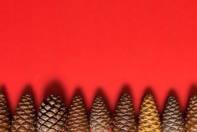 Mehrfarbige tannenzapfen angeordnet in einer reihe am unteren rand des bildes mit weichem schatten auf rotem hintergrund mit leerem raum für weihnachtsentwurf
