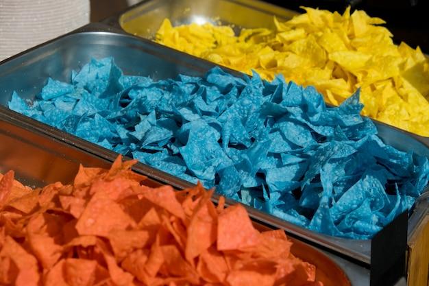 Mehrfarbige tortillachips in schalen auf der vitrine. streetfood-festival. selektiver fokus.