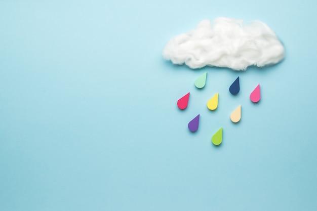 Mehrfarbige tropfen fallen aus einer wolke auf eine blaue oberfläche