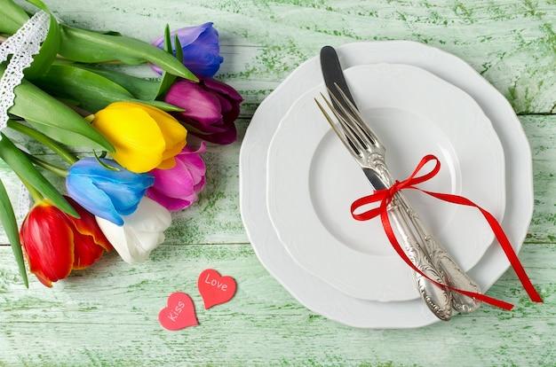 Mehrfarbige tulpen auf einem schäbigen grünen tisch. regenbogen der blumen. speisekarte