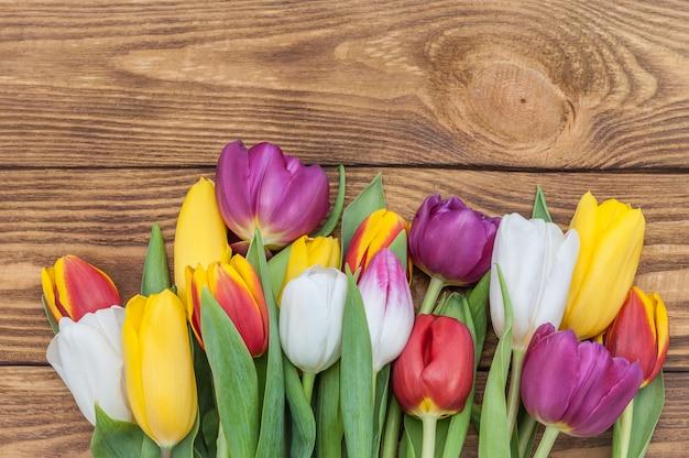 Mehrfarbige tulpen mit einem arm voll in der mitte gegen einen hintergrund des hellen holzes.