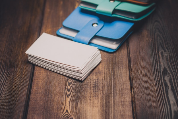 Mehrfarbige visitenkartenhalter auf einem copy space aus holz und weißem papier.