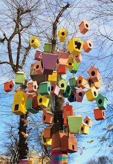 Mehrfarbige vogelhäuser auf den niederlassungen eines baums
