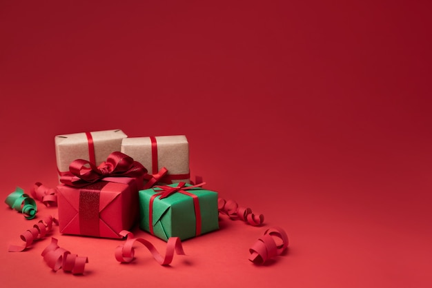 Mehrfarbige weihnachtsgeschenke auf rotem hintergrund urlaubsgrüße konzept kopie raum