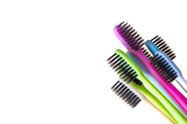 Mehrfarbige zahnbürsten mit schwarzen borsten auf weißem grund. Premium Fotos