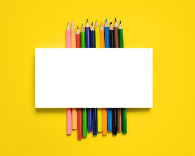 Mehrfarbige zeichenstifte auf gelbem hintergrund, mit platz für ihren text