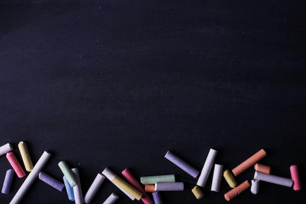 Mehrfarbige zeichenstifte liegen auf einer schwarzen tafel