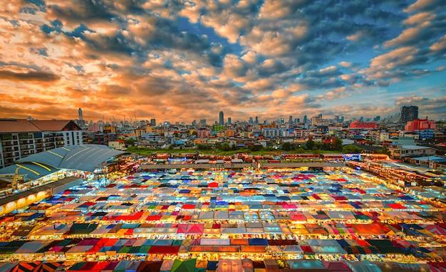Mehrfarbige zelte im markt trainieren einen gebrauchtmarkt bei sonnenuntergang in bangkok, thailand