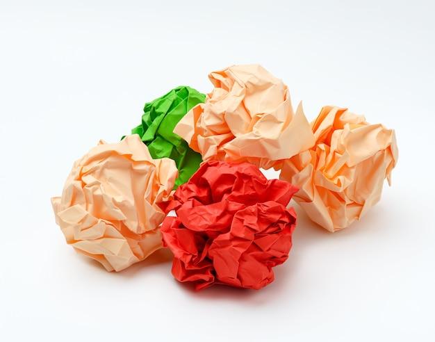Mehrfarbige zerknitterte papierkugeln auf weißer oberfläche, rot, grün und pink