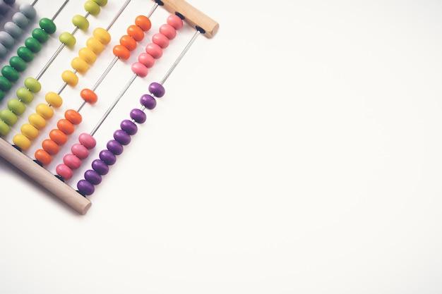 Mehrfarbiger designer-hintergrund. berechnung des bunten hölzernen regenbogenabakus für die zahlenberechnung. holzabakus auf weißem hintergrund hautnah. lernkonzept mathematik.