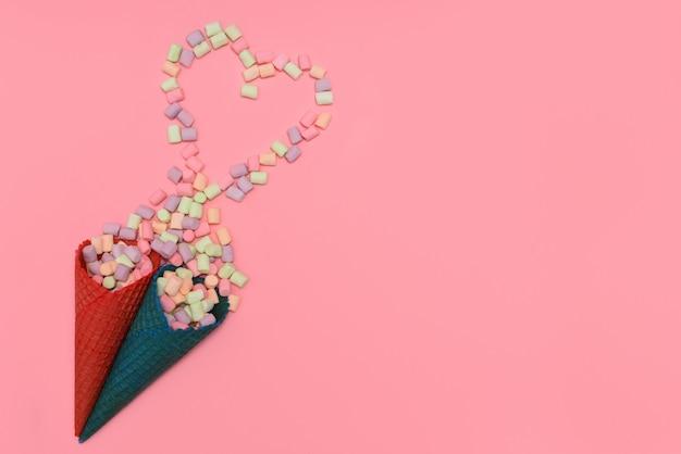 Mehrfarbiger eibisch fiel von zwei waffelschalen auf rosa hintergrund