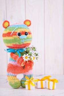Mehrfarbiger gestrickter bär mit geschenken und blumen. gestricktes spielzeug, amigurumi, kreativität, diy