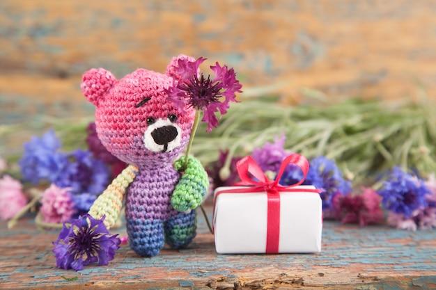 Mehrfarbiger gestrickter kleiner bär mit kornblumen auf einem alten hölzernen hintergrund.