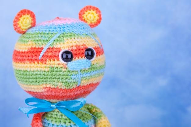 Mehrfarbiger gestrickter teddybär mit geschenken und blumen. gestricktes spielzeug, handgemacht, amigurumi, kreativität, diy