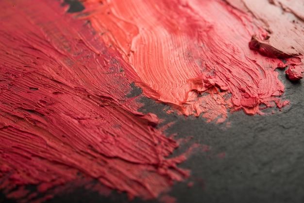 Mehrfarbiger lippenstift auf schwarzer oberfläche