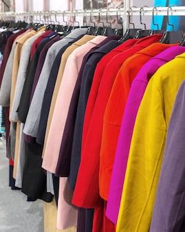 Mehrfarbiger mantel, der an den aufhängern hängt
