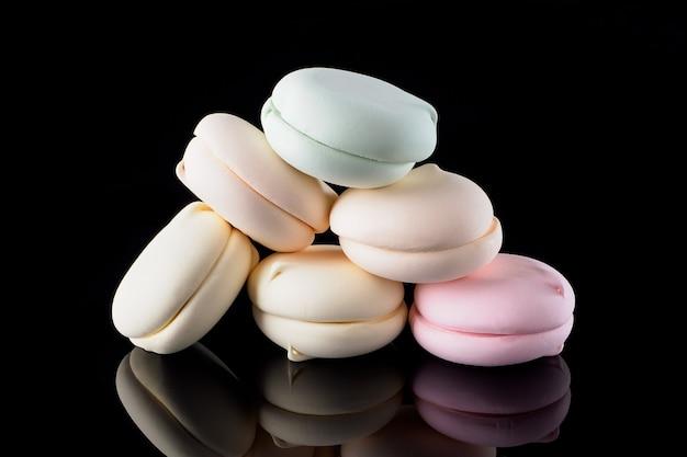 Mehrfarbiger marshmallow auf schwarzem hintergrund mit reflexion, pastell isoliert. schöner und bunter makronenhintergrund. heller hintergrund oder begrüßungsbildschirm. süßigkeiten kreatives trendkonzept.