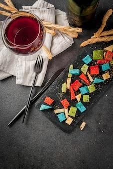 Mehrfarbiger organischer holland-käse mit brotstöcken und weinglas