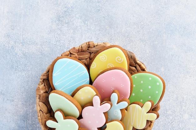 Mehrfarbiger oster-lebkuchen, süßigkeiten und verstreutes süßwaren-dressing auf grauem tisch. ostern backtisch. feierliches tischkonzept. platz für text.