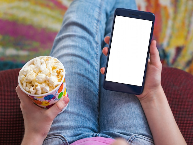 Mehrfarbiger pappbecher mit popcorn in den händen des mädchens.