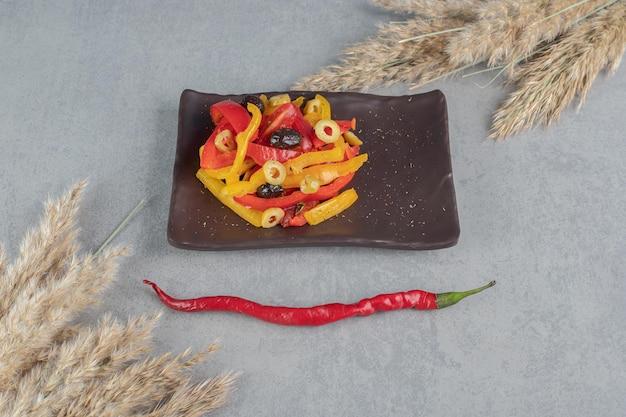 Mehrfarbiger paprikasalat mit schwarzen und grünen oliven.