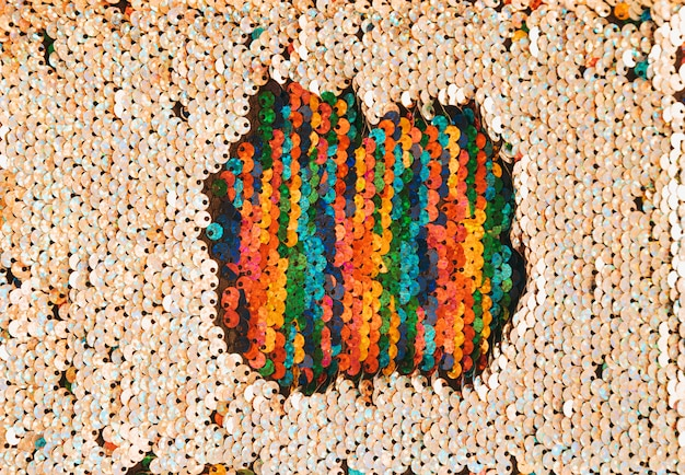 Mehrfarbiger patch mit pailletten, umgeben von goldenen pailletten