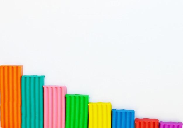 Mehrfarbiger plasticine gelegen auf einem weißen hintergrund. kinder spielzeug hintergrund. rahmen mit platz für text.