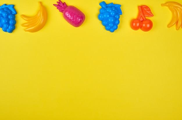 Mehrfarbiger plastik spielt früchte auf einem gelb