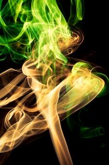 Mehrfarbiger rauch auf schwarzem hintergrund.