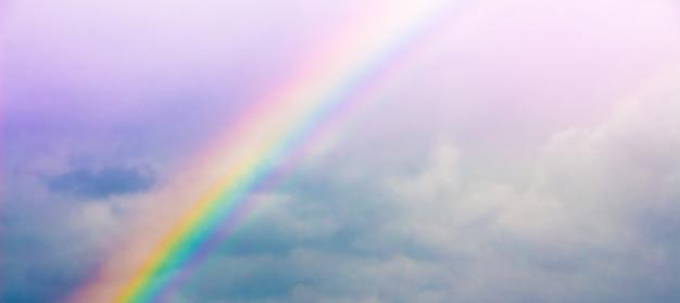Mehrfarbiger regenbogen am bewölkten himmel nach einem gewitter